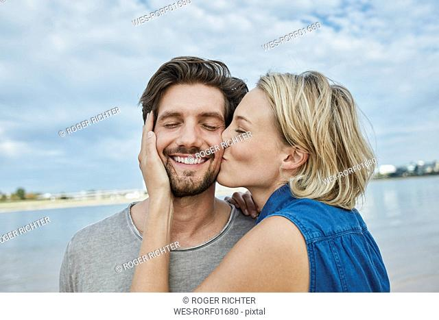 Happy young couple kissing on the beach