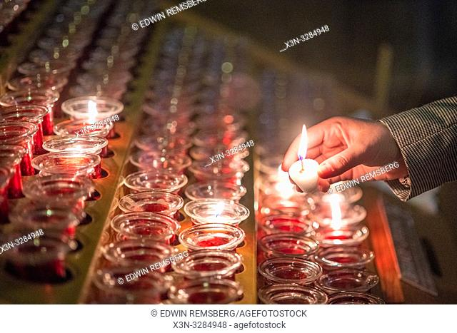 lighting votive candles at Notre-Dame de Paris, medieval gothic cathedral in Paris, France, a few weeks before destruction by fire