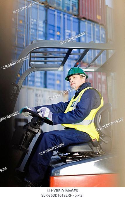 Worker using machinery in shipping yard