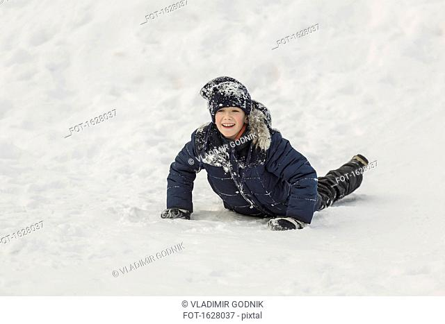 Cheerful boy looking away while lying in snow