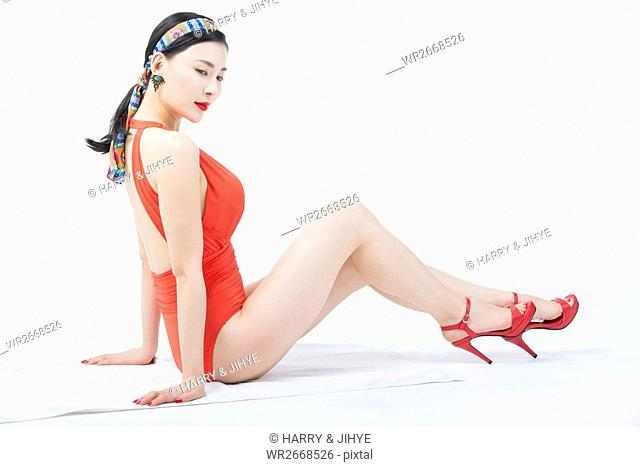 Side view of young woman in red swimsuit posing sitting down