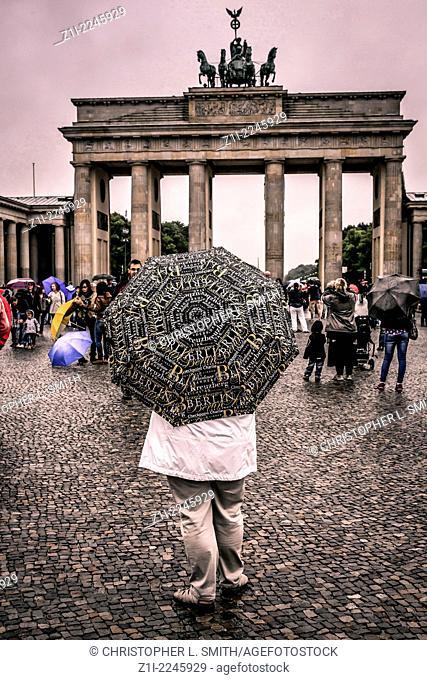 Woman standing with a Souvenir Berlin Umbrella near the Brandenburg Gate