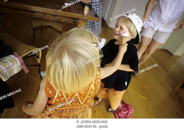A little boy and a little girl, 1-5 years old, indoor, bedaubing each other with ice cream