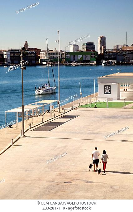 Couple walking with dogs near the Veles e Vents building at the port Marina Real Juan Carlos I with a sailing boat at the background, Valencia, Spain, Europe