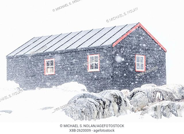 Restored British Research Base A in a snow storm at Port Lockroy, Antarctica