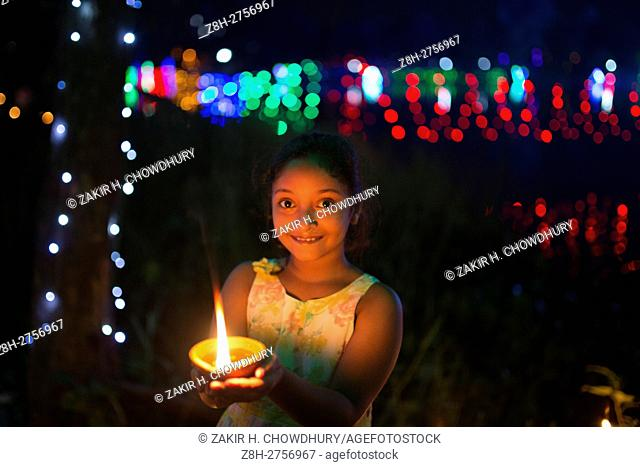 DHAKA, BANGLADESH - OCTOBER 29 : Children lights oil lamps during the 'Deep Utsav or Light festival' at the historical Gauhar Mahal palace