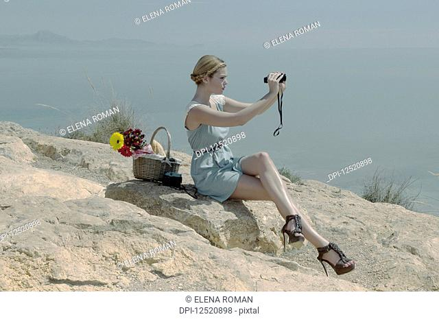 A young woman in stiletto heels sits on a rock with a picnic basket using binoculars on the coast; Spain