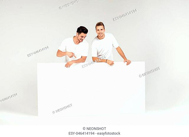 Two young handsome guys holding blank white banner, signboard, isolated on white studio background