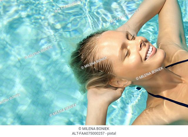 Woman floating in pool with eyes closed