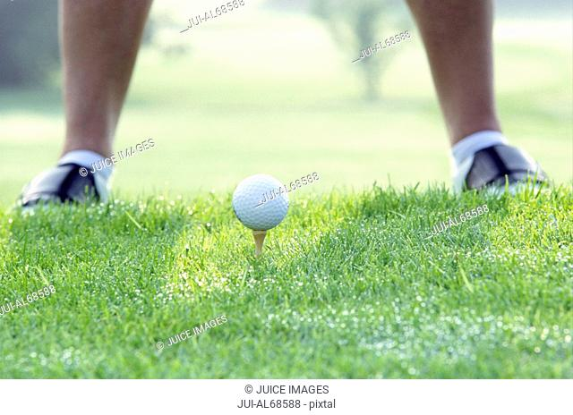 Detail view of a man standing in front of a teed golf ball in the grass