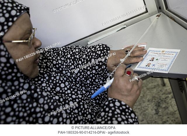 dpatop - Egyptian woman ticks his ballot on the first day of the 2018 Egyptian presidential elections, at a polling station, in Cairo, Egypt, 26 March 2018