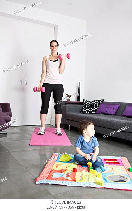 A young mother exercising at home whilst her baby son plays on the floor