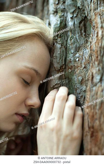 Young woman leaning forhead against tree trunk, eyes closed