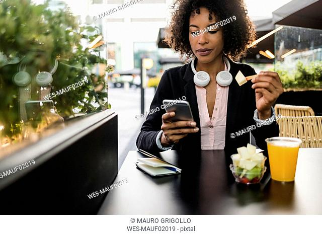 Portrait of businesswoman looking at cell phone at pavement cafe while eating fruit salad