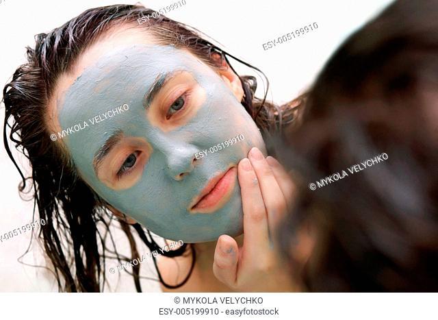 Woman putting a mud mask