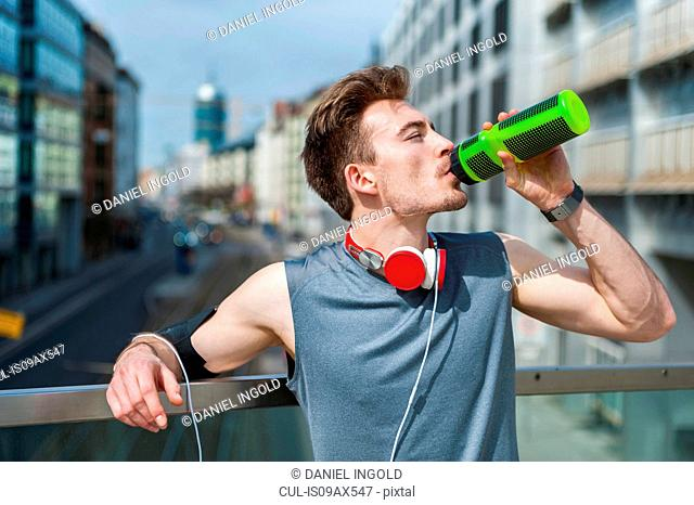 Young man taking a break from exercise, standing on bridge, drinking from water bottle