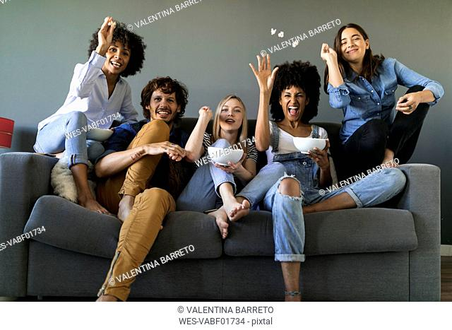 Exuberant friends sitting on couch watching tv