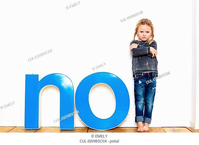 Young girl standing next to large three-dimensional letters, spelling the word NO