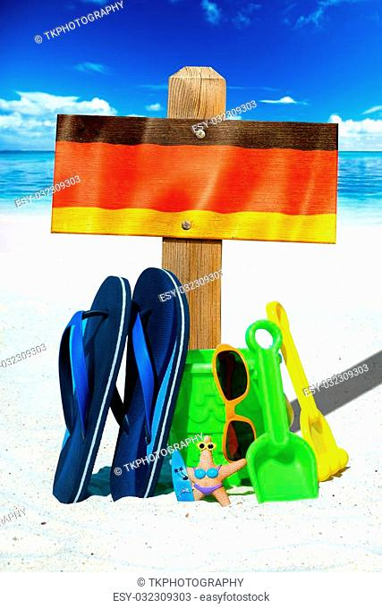 Wooden sigboard with the german flag, blue flip flops and colorful beach toys on the sunny beach