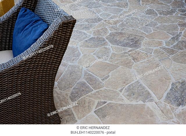 Close-up of stone floor with cropped wicker chair