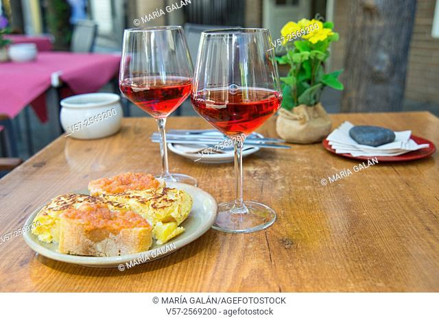 Two glasses of rose wine with tapa of Spanish omelet and tomato sauce in a terrace. Madrid, Spain