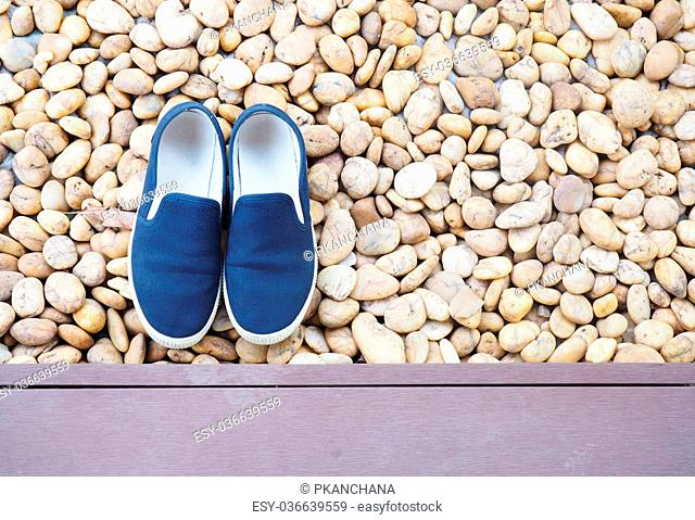 blue Sneaker shoe took off on stone background, slip-on shoes