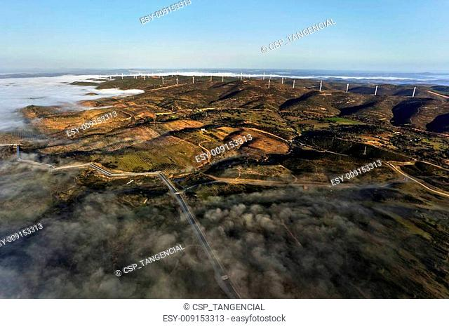 Aerial view of landscape with clouds and windmills on the horizon