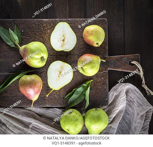 fresh ripe green pears lie on a brown wooden board, top view