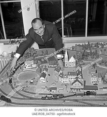 Ein Mann ist versunken ins Spiel mit seiner Modelleisenbahn, Deutschland 1950er Jahre. A man playing musingly with his model train, Germany 1950s