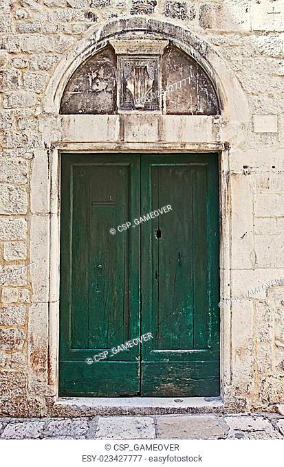 Ancient door painted green with architrave