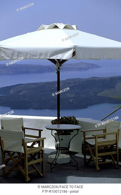 Sun shade with chairs on a terrace in front of a boarder, Greece, Santorin