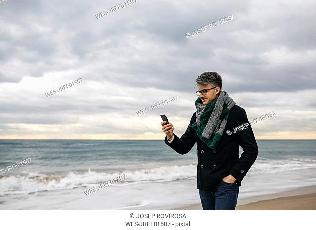 Businessman on the beach looking at cell phone