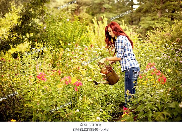 Gardener watering plants in backyard
