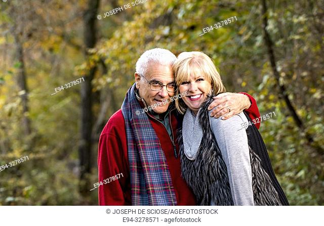 A happy 65 year old man and a 59 year old blond woman laughing and walking in a forest setting, smiling at the camera