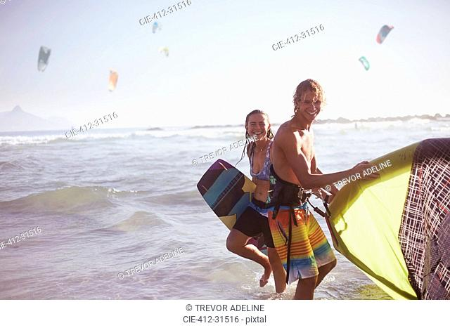 Portrait smiling couple with kiteboarding equipment in ocean surf