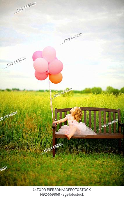 Girl, age 3 looking at balloons