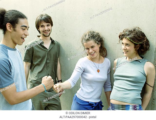 Four young friends standing next to wall, two touching fists