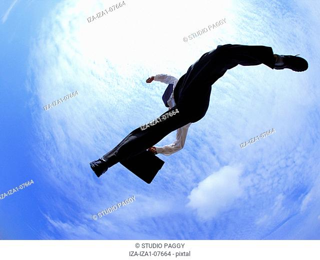 Low angle view of a businessman jumping in mid-air