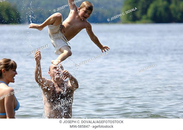 Father throwing son into air on lake