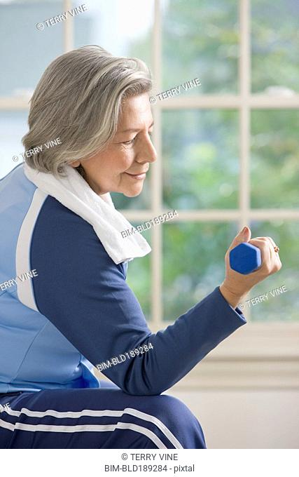 Senior Hispanic woman lifting hand weights