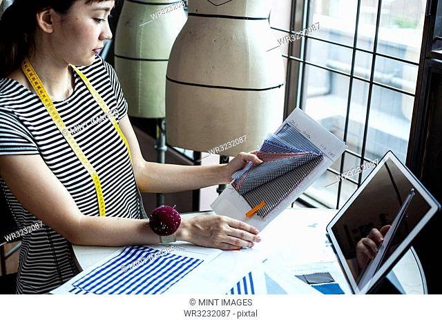 Japanese female fashion designer working in her studio, sitting at table, looking at fabric samples