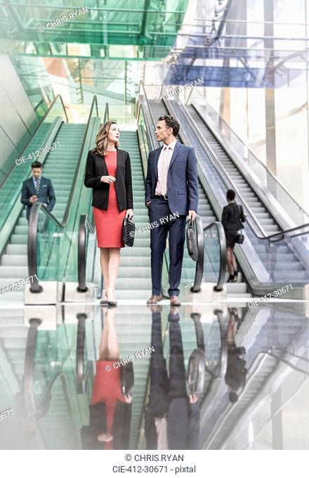 Corporate businessman and businesswoman talking below escalators in modern lobby
