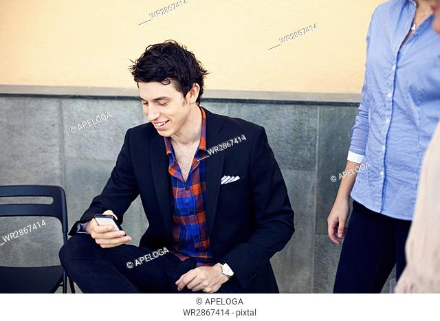 Smiling businessman using smart phone while sitting on chair outdoors