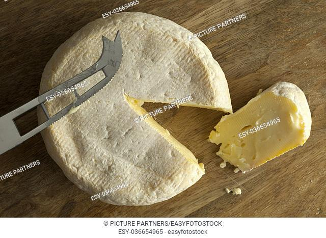 Reblochon de Savoie cheese from raw cows milk with a slice