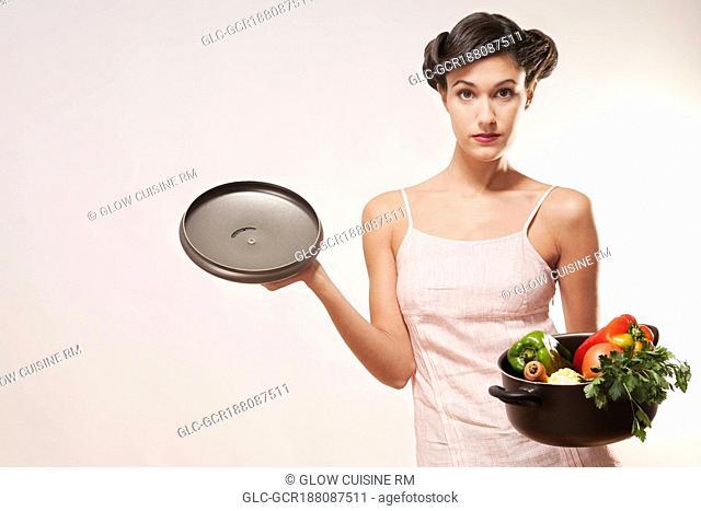 Portrait of a woman holding a pot of fresh vegetables
