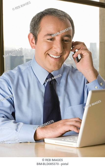 Hispanic businessman with laptop talking on cell phone