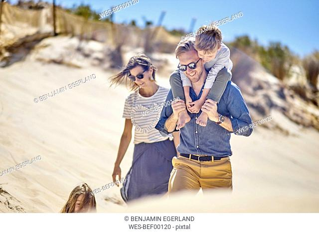 Happy family walking on the beach together