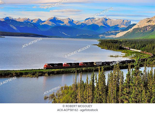 A Canadian National freight train traveling along Brule Lake in the foothills of the Rocky Mountains of Alberta Canada