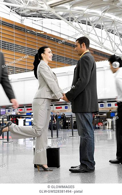 Businessman and a businesswoman standing at an airport with holding each other's hands