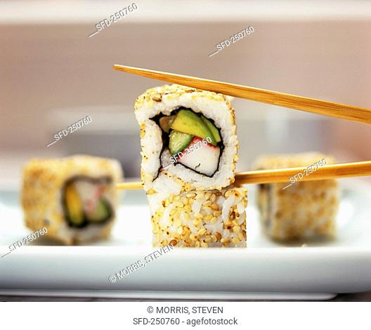 Several California rolls, one held in chopsticks